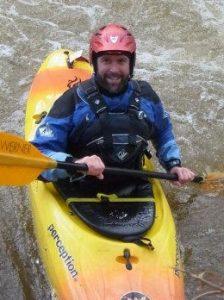Steve in Creek Boat smiling at camera